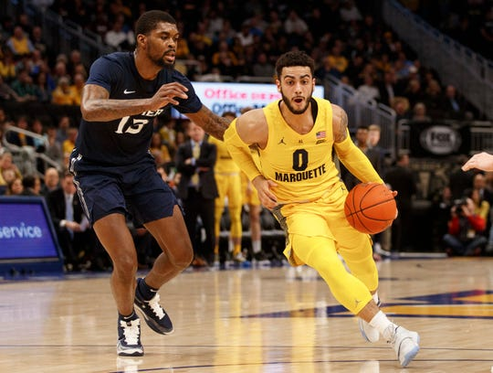 Jan 15, 2020; Milwaukee, Wisconsin, USA; Marquette Golden Eagles guard Markus Howard (0) drives for the basket around Xavier Musketeers forward Naji Marshall (13) during the first half at Fiserv Forum.