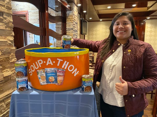 Rotarian Maria Arevalo Mojica donates the first can of soup.