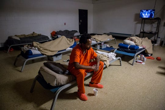 Haneef Tarrance sits on his cot in the former recreation room of the Coshocton Justice Center. Due to overcrowding issues, the room has been converted to house cots for 10 inmates.