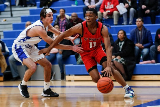 Orchard Lake St. Mary's guard Lorne Bowman Jr. (11) dribbles against Catholic Central guard Hayden Files (2) at Catholic Central High School in Novi, Tuesday, Jan. 14, 2020.