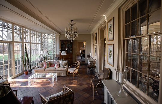 The large rear sunroom has its original tiled floor and its many-paned glass walls. Outside that glass decorative ironwork embellishes the scene from both inside and out .