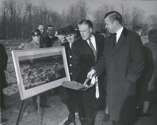 Gov. George W. Romney has a picture of Oakland Community College's future Orchard Ridge Campus before him as the break ground for the start of construction, with him are George Mosher (left) and John E. Tirrell