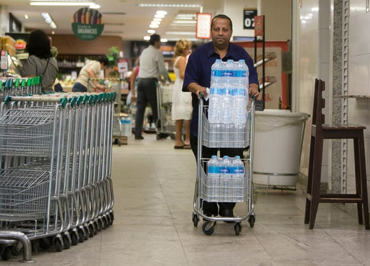Almir Vicente pushes his recently bought bottled water at a supermarket in the Copacabana neighborhood of Rio de Janeiro, Brazil, Wednesday, Jan. 15, 2020.