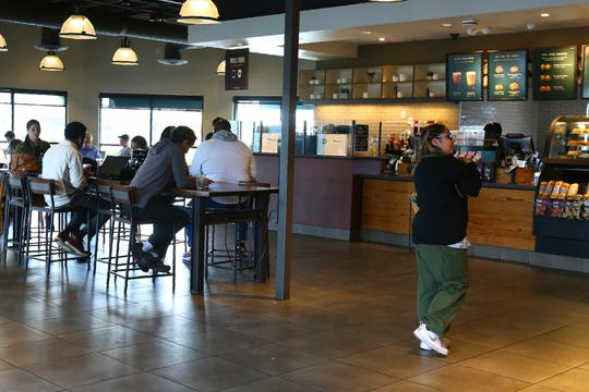 Patrons at a local Starbucks Community Store, in Phoenix. The larger Starbucks location has a community meeting space for events and programming, and offers local community hiring.