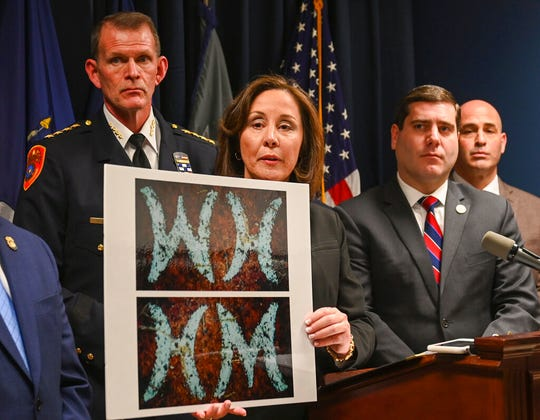 Suffolk County Police Commissioner Geraldine Hart shows a photograph with the initials on a belt, showing either an HM or WH, depending on the angle, during a press conference at police headquarters in Yaphank , N.Y., Thursday, Jan. 16, 2020.