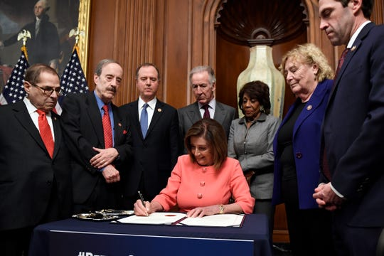 House Speaker Nancy Pelosi of Calif., signs the resolution to transmit the two articles of impeachment against President Donald Trump to the Senate for trial on Capitol Hill in Washington, Wednesday, Jan. 15, 2020
