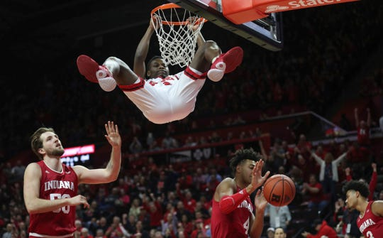 Rutgers guard Montez Mathis (23) hangs on the rim after this slam dunk.