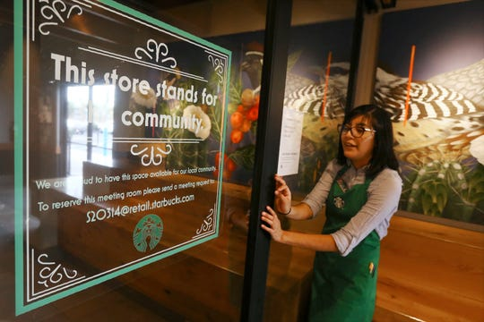 Belith Ariza, a barista trainer at Starbucks, opens the doors to the community meeting space at a local Starbucks Community Store, in Phoenix.