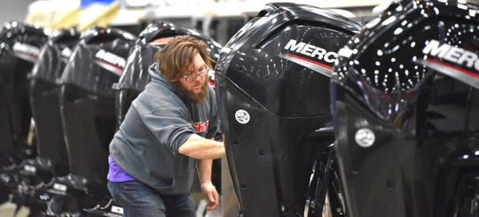 Anderson's Boat Sales employee Blake White waxes Mercury outboards on pontoon boats.