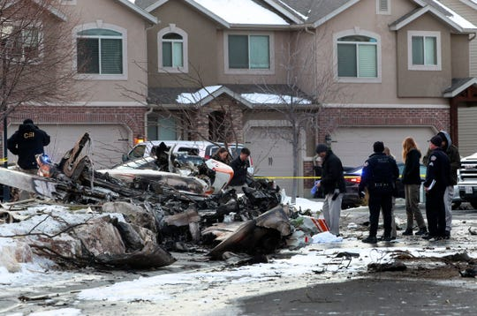 Emergency crews look through the debris from a small plane that crashed in a Roy, Utah, residential neighborhood, narrowly missing townhouses in the area, on Wednesday, Jan. 15, 2020.