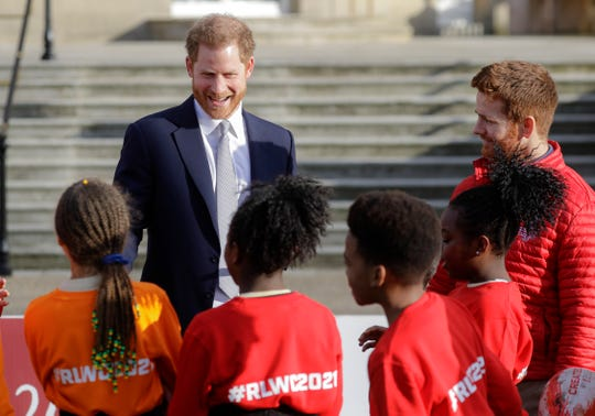 Britain's Prince Harry smiles at schoolchildren in the gardens at Buckingham Palace in London on Thursday.