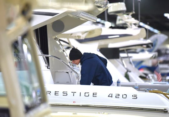 Colony Marine employee Austin Porter puts the finishing touches on a Prestige 420 S.