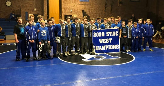 Horseheads wrestlers with their championship banner after clinching the STAC West title with a 60-17 win over Corning on Jan. 15, 2020 at Horseheads High School.