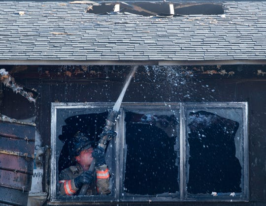 An Evansville firefighter puts water under the eaves of an apartment fire at 3955 Vista Court in the Buena Vista Apartments Thursday morning, Jan. 16, 2020.