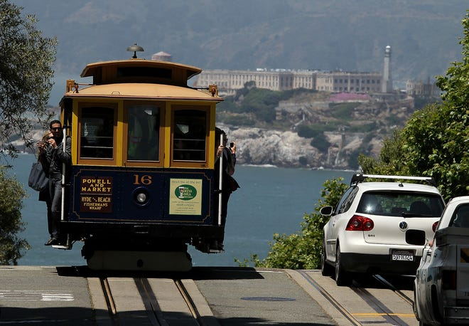 One of San Francisco's famed cable cars travels along Hyde Street, with Alcatraz in the background.