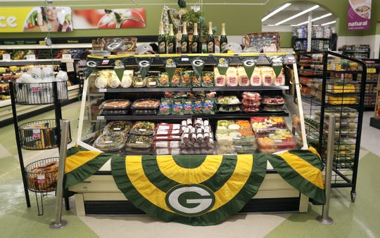 A Green Bay Packers-themed display at Festival Foods in Bellevue on Jan. 16, 2020, features a variety of tailgating essentials, such as fruit and vegetable trays, taco dip, cheese and sausage, hand warmers and Packers cups, napkins and baked goods.
