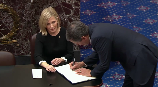 "Sen. Steve Daines, R-Mont., signs the oath book Jan. 16 after promising to uphold ""impartial justice"" as President Donald Trump's impeachment trial gets underway."