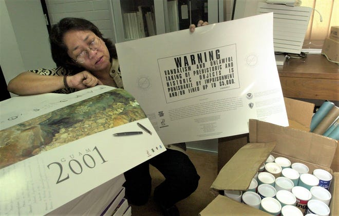 In this August 2001 file photo,  Guam Historic Preservation Officer Lynda Aguon holds newly arrived posters in the Guam Historic Resources Division office. The posters, with a warning on the back, aim to educate the public against vandalism and looting of cultural resources.