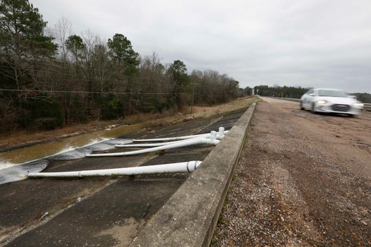A car speeds past the additional drainage pumps on the Oktibbeha County Lake dam near Starkville, Miss., Wednesday afternoon, Jan. 15, 2020. Officials are hoping the additional drainage will limit the heavy pressure the rain-swollen lake is placing on the dam. County officials believe a breach would affect an estimated 130 properties and several highways.