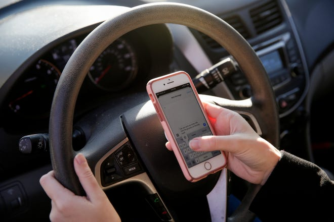 PHOTO ILLUSTRATION -- Indiana Gov. Eric Holcomb has called for a ban on use of hand-held cellphones while driving.