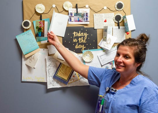 Sarah Schutz, a nurse in the burn center at Our Lady of Lourdes Medical Regional Center, shows off thank you cards on the unit's bulletin board.