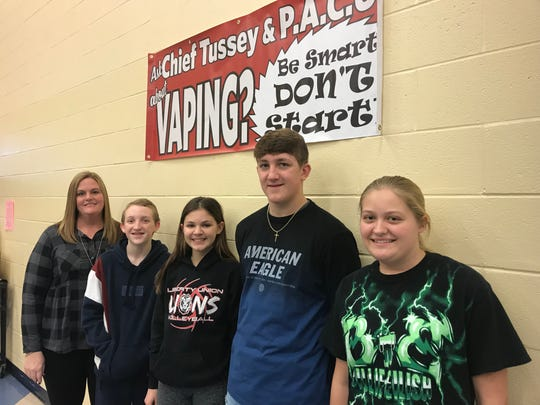 LIberty Union Middle School assistant principal Holly Griffin and students Matthew Hinton, Payton Hochradel, Slade McClaskey and Abby Griffin stand under an anti-vaping sign at the school. The initials P.A.C.U. on the sign stand for Police and Citizens United.