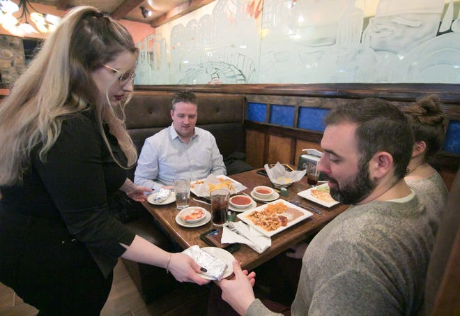 Maxx Emerick serves a meal to, from left, Mike Dabbs, Chris and Katie Rodela Thursday, Jan. 16, 2020 at the recently-opened Don Juan Mexican Restaurant in the Green Oak Township Village Place shopping center.