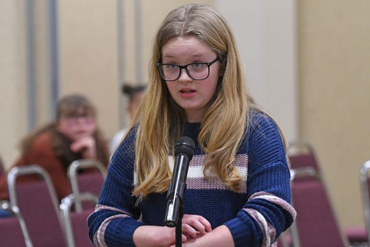 """Addison Sigler, a sixth grader at Lexington, uses her finger to spell the word out on her arm as she spells it out loud to the pronouncer Thursday morning during the Richland County Spelling Bee. Sigler won the contest with the word """"eucalyptus."""""""