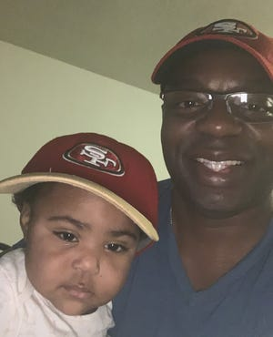 Paul Lamar Hunter poses with his 1-year-old granddaughter Khloe. Paul was one of 21 children in his Racine family and the only non-Packers fan of the bunch.