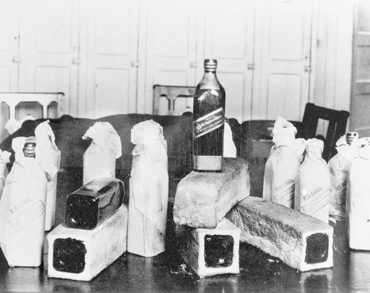 Bottles of Scotch whiskey smuggled in hollowed-out loaves of bread are pictured in this June 12, 1924, file photo. Statistically, Prohibition was not an utter failure. Deaths from alcohol-related cirrhosis declined, as did arrests for public drunkenness.