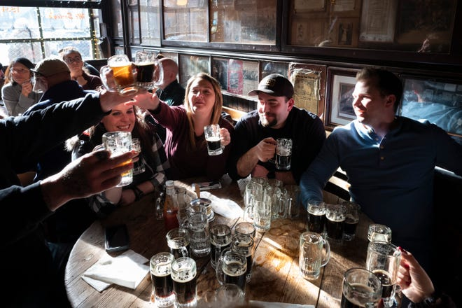 Customers raise their mugs of beer in McSorley's Old Ale House in New York in this December 2019 photo. The Irish bar opened in the mid-19th century and was a speakeasy during Prohibition.