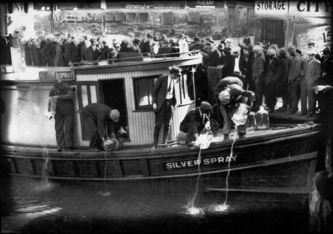 """Spectators gather by the side of the Silver Spray, a captured run runner, as they watch Prohibition agents pour """"white lightning"""" from the five-gallon bottles into the Elizabeth River, in Norfolk, Va. in 1922. The Prohibition Era, which lasted from Jan. 17, 1920, until December 1933, is now viewed as a failed experiment that glamorized illegal drinking."""