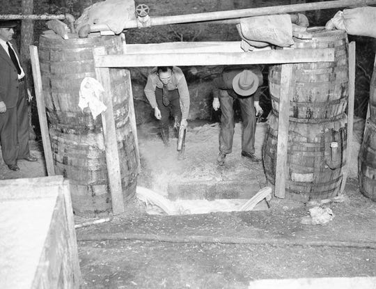 In this May 5, 1937, photo, federal agents raided a large-scale bootlegging operation near Griffin, Ga. They then broke up equipment and destroyed materials on hand.
