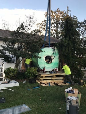 Workers use a crane to move the MRI machine at Knox Orthopaedics. The clinic recently installed a Siemens Magnetom Espree MRI unit that provides greater patient comfort.