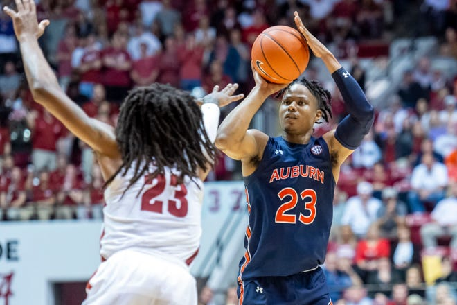 Auburn forward Isaac Okoro (23) shoots a 3 as Alabama guard John Petty Jr. (23) defends on Wednesday, Jan. 15, 2020, in Tuscaloosa, Ala.