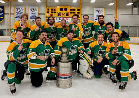 Former Bachelorette contestant Jason Tartick, front right,  poses with his Jagr Bombers teammates after they won the Nashville adult rec league championship Tuesday night at Ford Ice Center in Antioch