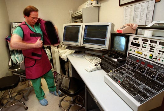 Dr. Carmine Sorbera, a cardiologist at Westchester Medical Center, puts on a lead apron before begining a heart procedure called an Electrophysiology Study in the cardiac catheterization lab. The lead apron will protect him from radation during the procedure. The instruments in the room are heart monitors. ( Stephen Schmitt / The Journal News 3/2/2000 ) sh