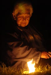 Barbara Crandell, of Thornville, lights sage at a gathering to welcome the summer season on the Observatory Mound at the Octagon Earthworks in Newark. The Cherokee woman was arrested in 2002 for trespassing at Moundbuilders Country Club. She died in November.