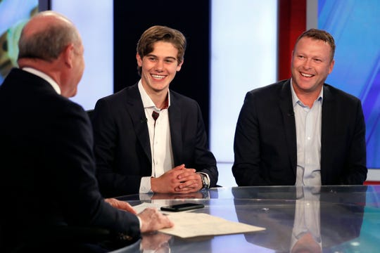 """New Jersey Devils forward Jack Hughes, center, the No. 1 overall pick in the 2019 NHL draft, and Devils Senior VP of Business Development and Hall of Fame goaltender Martin Brodeur, right, appear on the Fox Business Network """"Varney & Co.,"""" with host Stuart Varney in New York, Monday, June 24, 2019."""