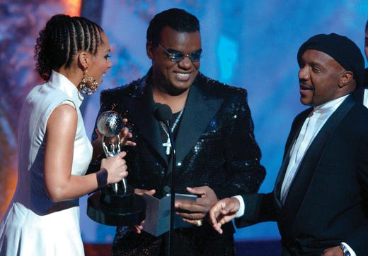 """Singer Alicia Keys, left, accepts her award as outstanding new artist, for """"Fallin',"""" from the Isley Brothers at the NAACP Image Awards in Los Angeles, Saturday, Feb. 23, 2002. Keys also won for outstanding album for """"Songs in A Minor."""" (AP Photo/Lucy Nicholson)"""