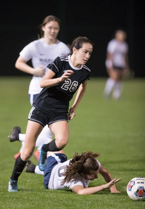 Sophia Nguyen (26) drives past a fallen Marlins defender during the Arnold vs Pensacola High School girls soccer at Ashton Brosnaham Park in Pensacola on Wednesday, Jan. 15, 2020.