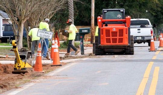 Crews work on the Hamilton Bridge Road sidewalk project at the corner of Hamilton Bridge Road and Emerald Drive in Pace on Thursday.