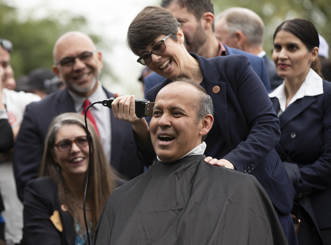 State Senator Robert Meza gets his head shaved by State Representative Jennifer Pawlik during a press conference in support of legislation to provide legally mandated insurance coverage to fire fighters who suffer from cancer brought on by exposure to carcinogenic chemicals in the line of duty. The event was held on the great lawn at the state capitol in Phoenix on Jan. 16, 2020.