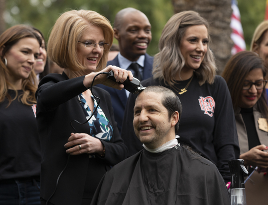 State Sen. Paul Boyer gets his head shaved by State Rep. Heather Carter during a press conference in support of legislation to provide legally mandated insurance coverage to firefighters who suffer from cancer brought on by exposure to carcinogenic chemicals in the line of duty. The event was held on the great lawn at the Arizona Capitol in Phoenix on Jan. 16, 2020.