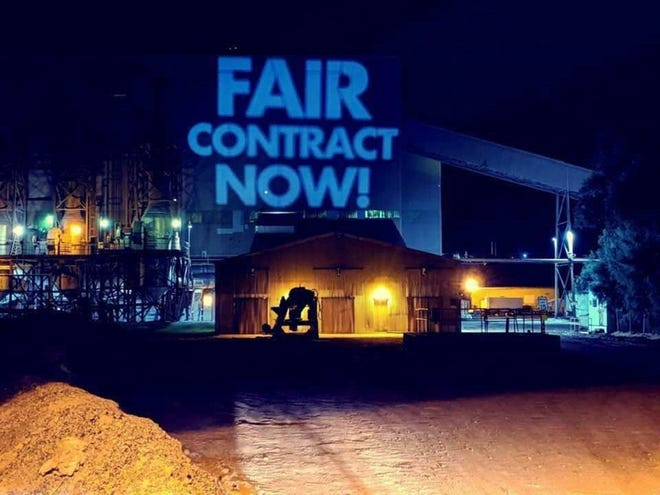 Striking members of the United Steelworkers showcase their demands by projecting them on to the side of an Asarco facility in Hayden.