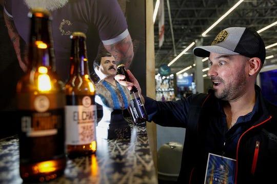 Un hombre observa una botella de cerveza artesanal de la marca El Chapo 701, durante la expo Intermoda que se celebra en la ciudad de Guadalajara, en Jalisco.