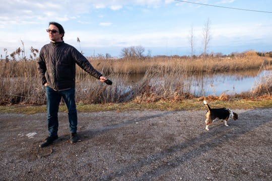 Josh Whiting, of the Blue Water Indigenous Alliance, walks his beagle Shiloh through a piece of property the organization is considering purchasing Wednesday, Jan. 15, 2020, in Port Huron Township.