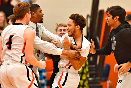 Central York's Kai'ryn Brown, center, is surrounded by his teammates after he hit a couple of huge shots in overtime to help the Panthers to a 69-67 win over Northeastern during boys' basketball action at Central York High School in Springettsbury Township, Wednesday, Jan. 15, 2020. Dawn J. Sagert photo