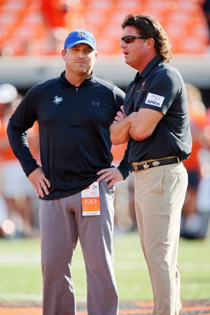 Head coach Sterlin Gilbert of the McNeese State Cowboys talks with head coach Mike Gundy of the Oklahoma State Cowboys before their game on September 7, 2019 at Boone Pickens Stadium in Stillwater, Oklahoma. Gilbert is the new offensive coordinator and quarterbacks coach at Syracuse.