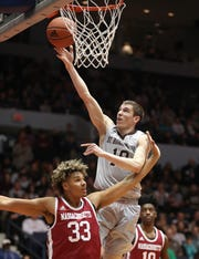 St. Bonaventure's Bobby Planutis drives to the basket over UMass's Tre Mitchell at the Blue Cross Arena.